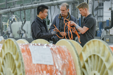 Cable coils with orange wires and three employees