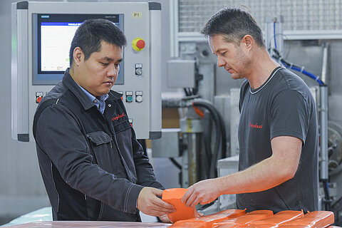 Two employees with an orange silicone compound