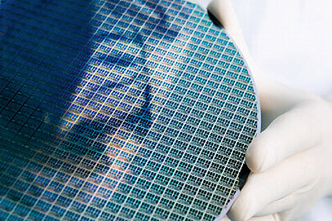 An employee handling a silicon wafer